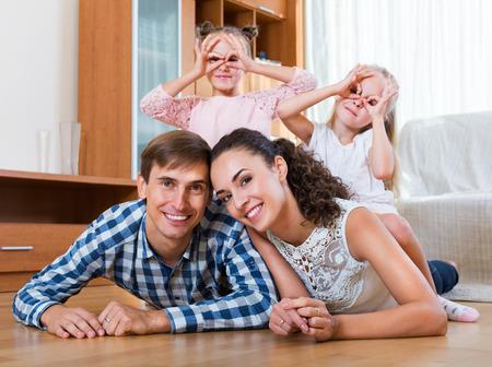 HAPPY FAMILY: Positivo relajado de cuatro posando en el interior dom�stico Foto de archivo
