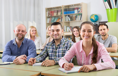 Glimlachende volwassen studenten van verschillende leeftijd bij uitbreiding cursussen in klaslokaal Stockfoto