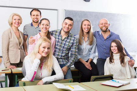 mature adult: Positive professor and cheerful group of students at extension courses. Focus on girl