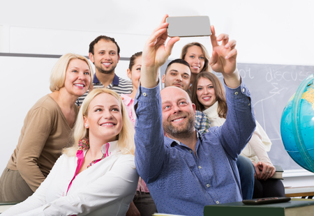 cohesive: american students of different age doing group selfie on smartphone