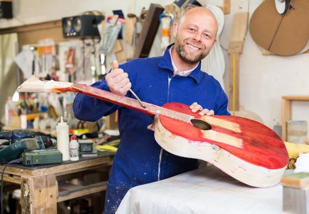 indoors: Portrait of happy smiling craftsman holding unfinished guitar indoors Stock Photo