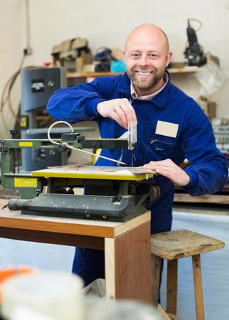 workroom: Positive professional woodworker on lathe at musical instrument workroom