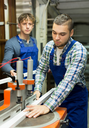 enginery: Two qualified men working on a machine in factory Stock Photo