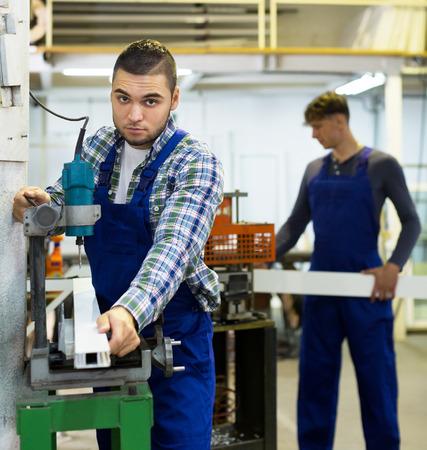 trabajadores: Dos j�venes trabajadores cuidadosos de trabajo en una m�quina en el taller de herramientas Foto de archivo
