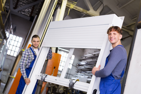 thermoplastic: Production workers in coverall with  PVC window with shutter at factory Stock Photo