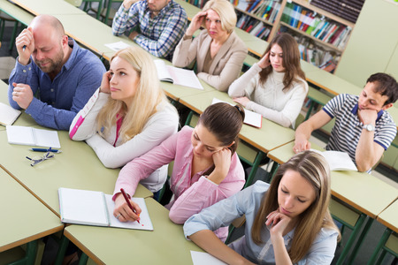 deadpan: Bored and tired adult students sitting at lesson in classroom