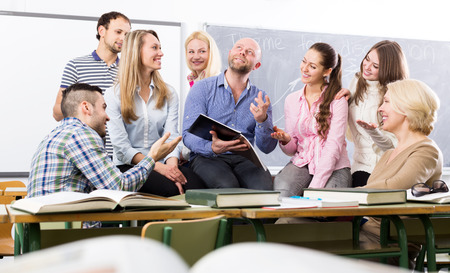 informal clothes: Teacher and cheerful adult students during break in classroom Stock Photo