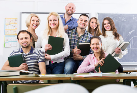 Portrait of friendly teacher and adult positive students in classroom