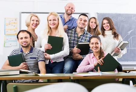 maestro: Retrato de maestros y estudiantes adultos positivos amistosos en el aula