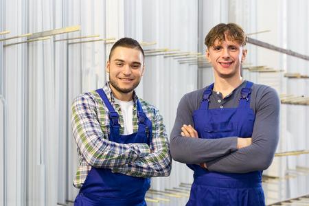 thermoplastic: Happy workmen near PVC window frames at factory