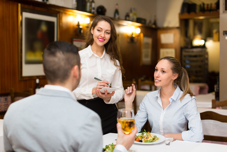 waitress: Cheerful waitress offering to young couple tasty dishes. Focus on girl