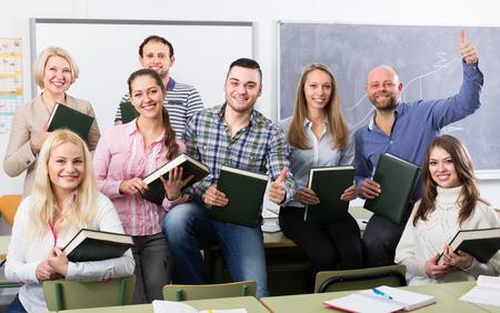 salon de clases: Sonriente mujer profesora y los estudiantes alegres posando en el aula en cursos de extensi�n