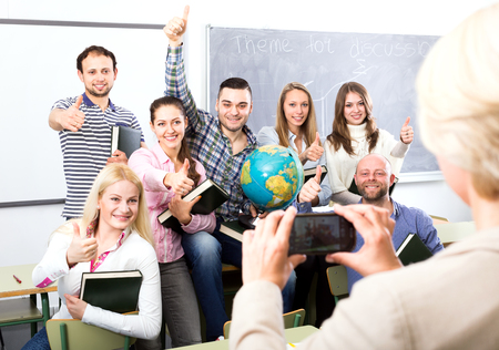 cohesive: Lecturer taking a photo of her happy smiling students with her new smart phone
