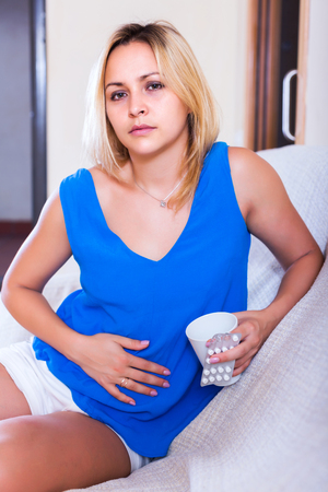 pains: Portrait of blonde girl with abdominal pains in home interior