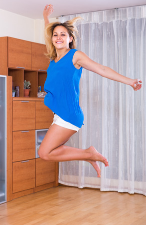 25s: Beautiful female jumping at home after receiving good news