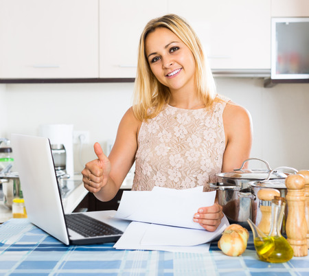 advantaged: russian blonde female signing documents at the kitchen Stock Photo