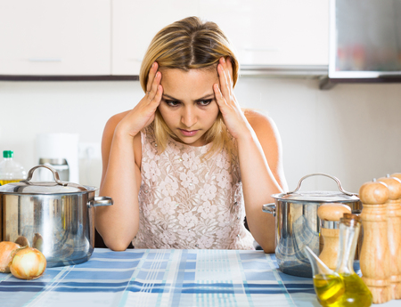 dispirited: Tired adult european woman leaning her elbows at the kitchen Stock Photo