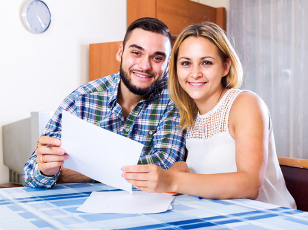 middle joint: Portrait of positive young woman and her husband with papers Stock Photo