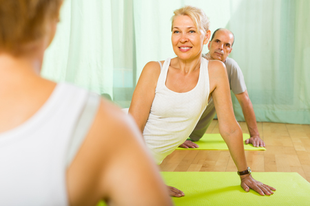 retirees: Positive smiling couple of retirees practicing body bending at gym Stock Photo