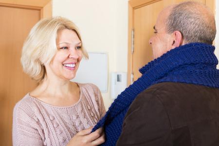 doorstep: Mature wife and pensioner husband talk at doorstep