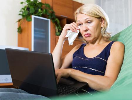mujer llorando: Ama de casa rubia madura llorando mientras ve la película de interior