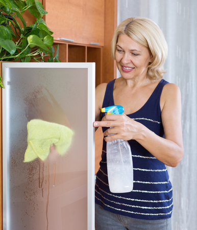 dusting: Smiling mature woman dusting glass of furniture at home