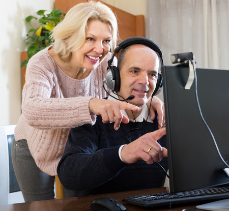 global retirement: Happy senior mature spouses using PC for video calls at home and smiling