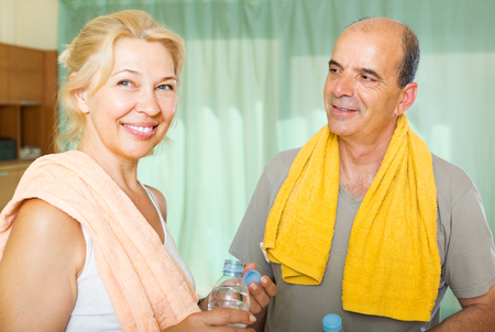 spouses: Happy mature spouses drinking water after fitness and smiling. Focus on man