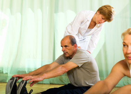 elderly: Positive yoga instructor showing new asana elderly couple