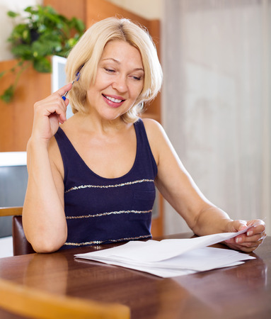 parsimony: Happy smiling mature woman filling in paper at home or office interior