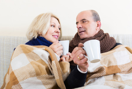 spouses: Mature loving spouses under blanket drinking tea on couch