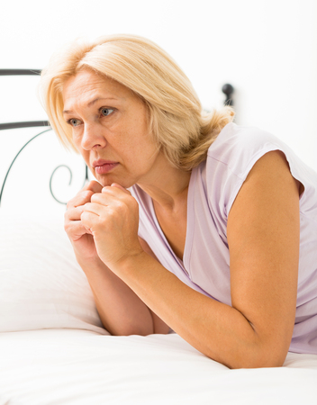 ennui: unhappy mature woman with head reclined upon hands in bed at bedroom
