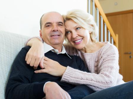 spouses: Portrait of happy senior spouses sitting on sofa indoor