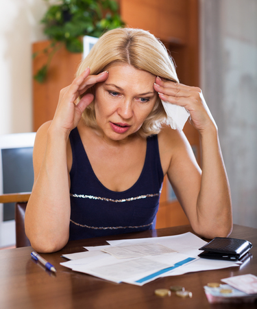 utility payments: Portrait of blond woman reading utility payments at the table in home or office
