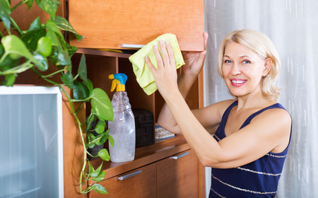 cleanser: Blonde smiling woman dusting wooden furniture with rag and cleanser at home