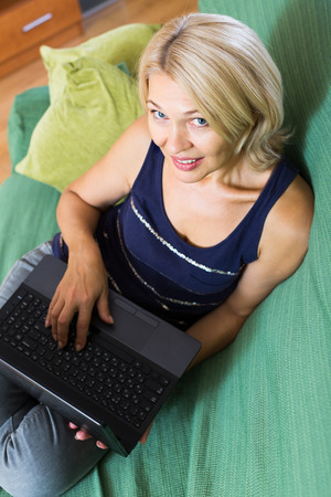 netbook: mature woman in blue with netbook sitting on sofa in living room