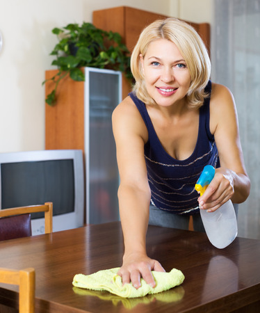 dusting: Mature blonde houswife dusting wooden furniture with rag and cleanser at home