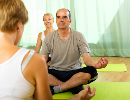 asana: Young  yoga  instructor showing asana to active senior attenders