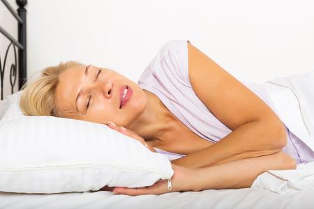 rubia: Hembra rubia madura en pijama de dormir con almohada blanca en la cama