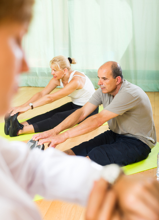 studio happy overall: Doctor keeping eye at elderly couple during training at gym. Focus on man Stock Photo