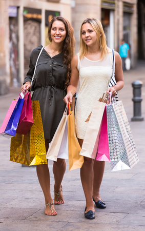 gladful: Two happy smiling young women walking by street with shopping bags