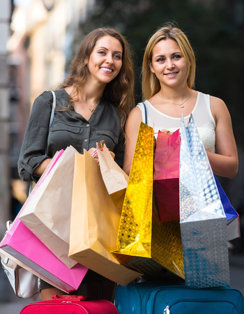 gladful: Two happy young female friends with shopping bags at street