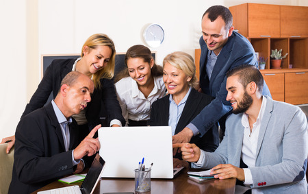 workplace wellness: positive european colleagues looking at laptop and smiling Stock Photo