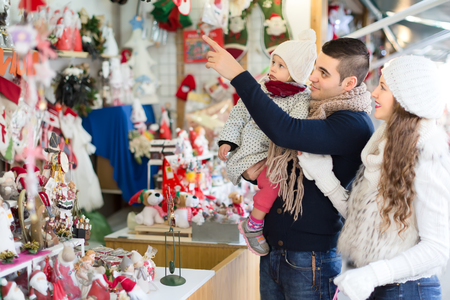 adviento: Un hombre con un hijo con su mujer est� de pie en un contador en una feria de navidad y se�alando a decoraciones de Navidad.