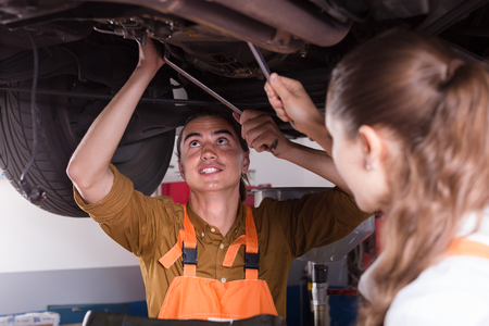 two car garage: Portrait of two smiling mechanics repairing car at garage. Selective focus on man Stock Photo
