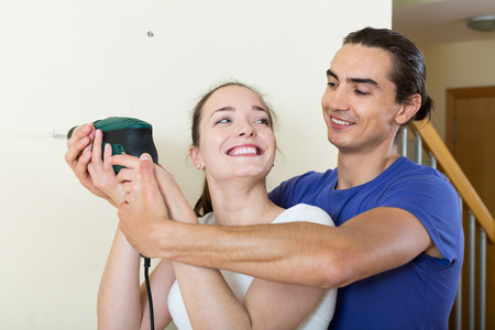 modifying: Young smiling couple drilling wall with drill at home