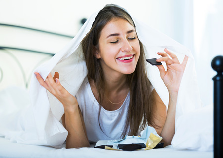 secret: Smiling girl secretely eating chocolate under blanket in bed