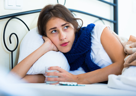 tonsillitis: Sad teenage girl with high fever and flu in bed Stock Photo