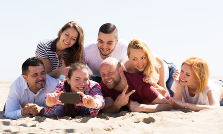 recollections: Cheerful friends of different age doing selfie at sea shore