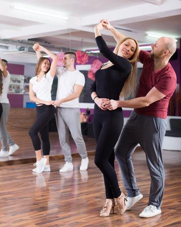 pareja bailando: Dos parejas jóvenes sonrientes que tienen clase de baile en el club Foto de archivo